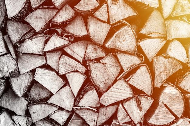 Текстурированный фон дров из рубленых дров для растопки и отопления дома. поленница со сложенными дровами. текстура березы. тонирован в черный белый или серый цвет. вспышка