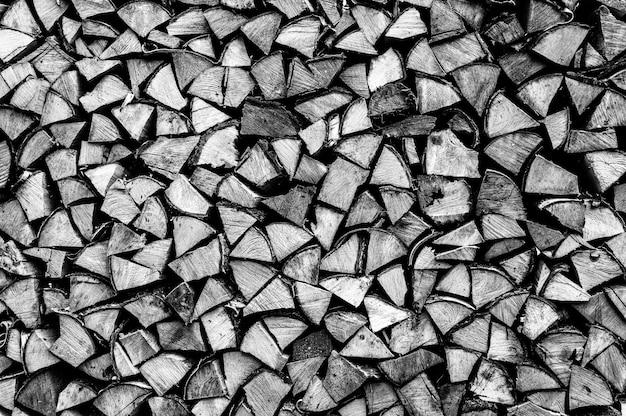 Текстурированный фон дров из рубленых дров для растопки и отопления дома. поленница со сложенными дровами. текстура березы. тонирован в черный белый или серый цвет