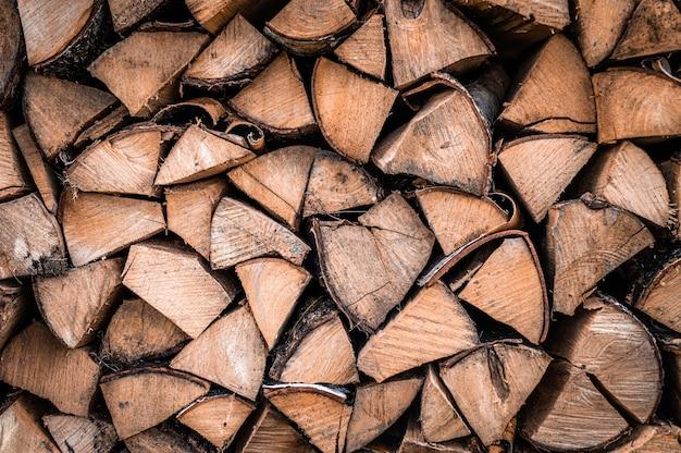 Текстурированный фон дров из рубленых дров для растопки и отопления дома. поленница со сложенными дровами. текстура березы