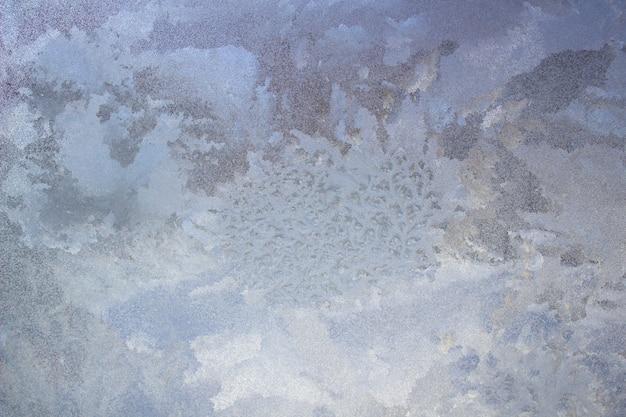 ガラスの織り目加工の霜パターン。冬の寒くて凍るような日に窓に氷の結晶。