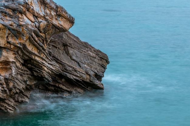 海のクローズアップによる織り目加工の岩