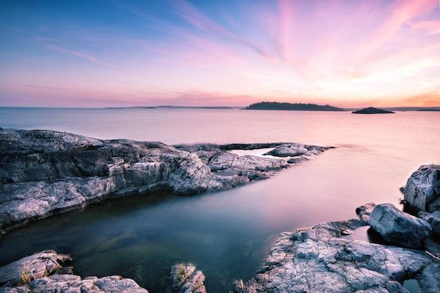 夜明けの空の下で織り目加工の石の島