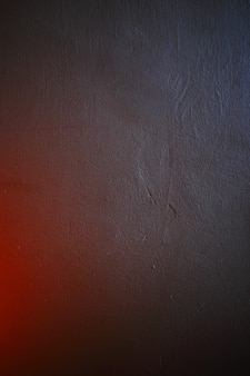 Textured stucco wall close up in colorful light.