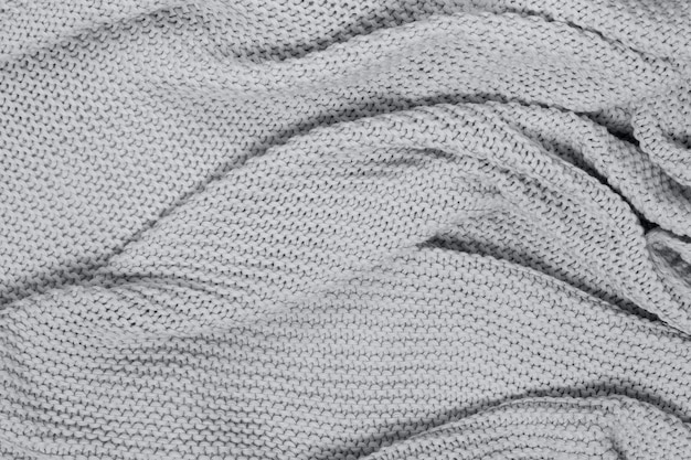 Textured surface of knitted cotton wave plaid, top view. seasonal cosiness flat lay. scandinavian minimal style. concept trendy color of year 2021 ultimate gray.