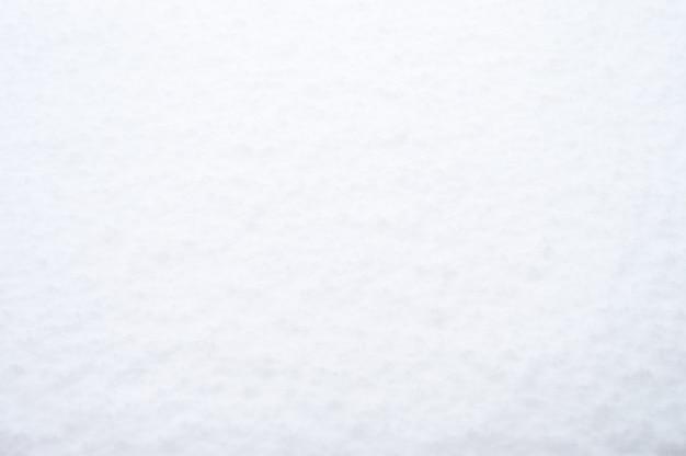 Текстурированная поверхность чистого чистого белого свежего снега в холодную снежную зиму. яркий естественный фон сельской местности. вид сверху, место для текста