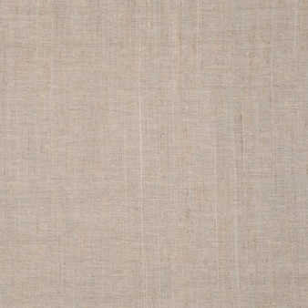 Textured textile background made of dense and rough light fabric with very fine detail and natural damage.