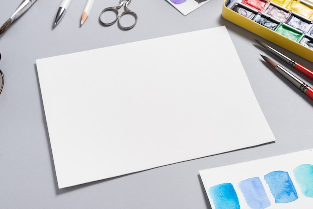 Textured watercolor paper sheet with paints on desk, mockup