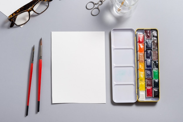 Текстурированный лист акварельной бумаги с красками на столе, макет