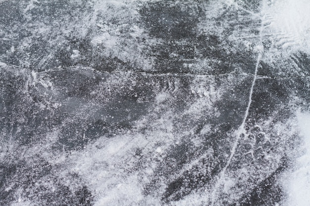 Texutured ise surface of frozen lake with cracks.