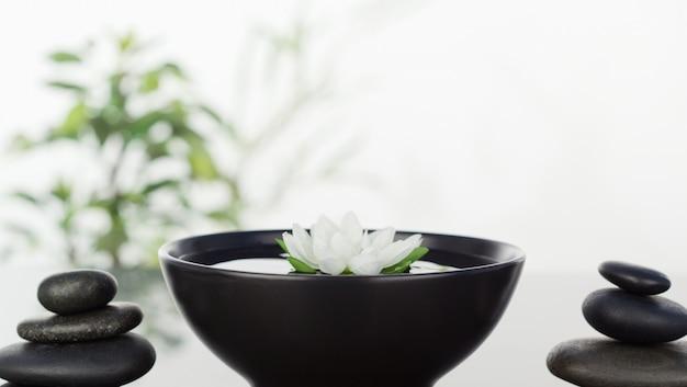 Thのボウルに浮かぶ白い花、両側の黒い小石の2つのスタック