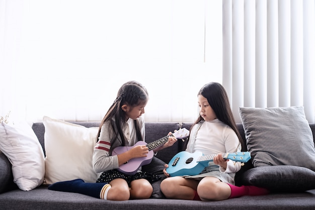 Th elder sister teaching younger sister for playing ukulele,with interested feeling,at living room,learning together,blurry light around
