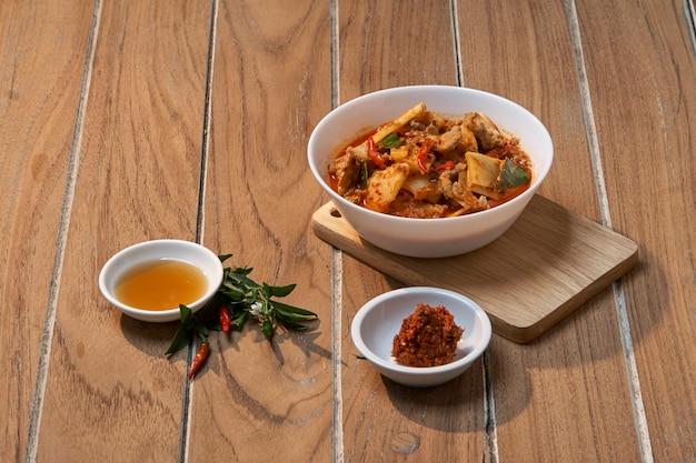 レッドカレー風味の豚肉、木製のバーケルの竹スライス、自然光、タイ料理th