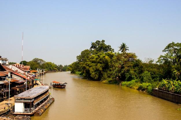 Tha chin川とボートの景色はタイの川に浮かんでいます。