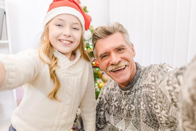 행복한 소녀와 할아버지가 셀카를 찍는다