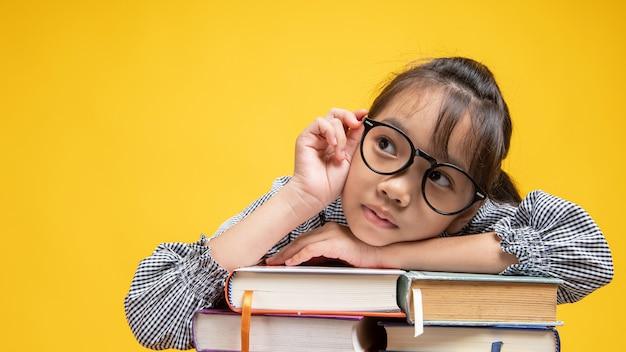 タイのアジアの女子学生が積み重ねられた本に落ちる、メガネに触れるとオレンジや黄色のスタジオで考えて