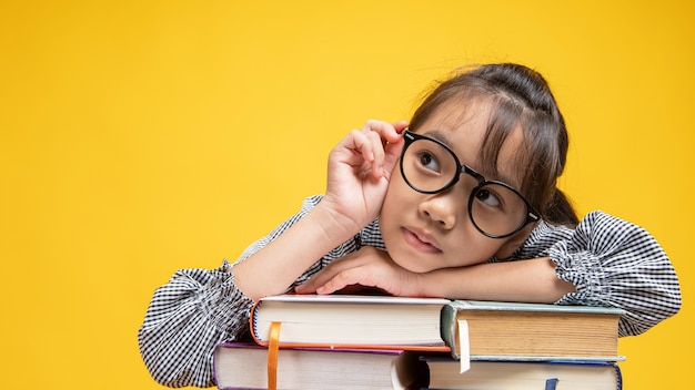 Thai asian girl student fall down on stacked book, touching glasses and thinking in studio on orange or yellow