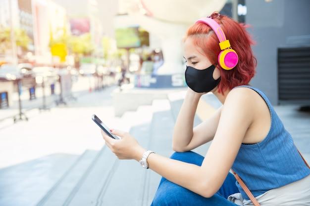 スマートフォンウェアのフェイスマスク、新しい通常のライフスタイルの人々の概念から音楽を聞いてサイアム公共スペースで自己隔離のために一人で座っているタイのアジアの女の子の十代。