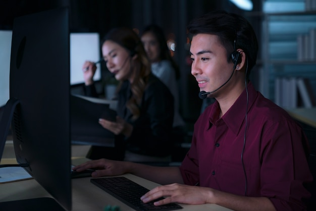 Thai asian man customer services care operators working night shift in call center