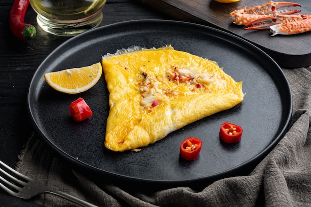 タイのアジアのオムレツ、新鮮な赤唐辛子、茶色と白のカニ肉、レモン、チェダーチーズと卵、プレート、黒い木製のテーブルの背景
