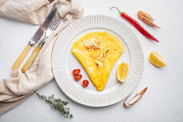 タイのアジアンオムレツ、新鮮な赤唐辛子、茶色と白のカニ肉、レモン、チェダーチーズと卵、プレート、白い背景、上面図フラットレイ