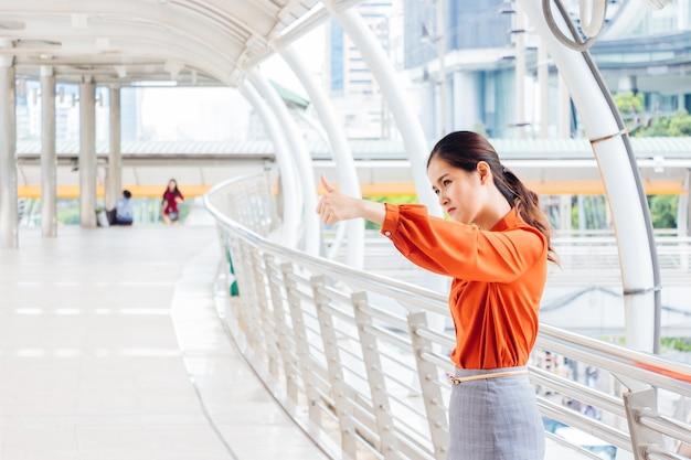 タイのアジア人女性がしゃがんで親指を立てる