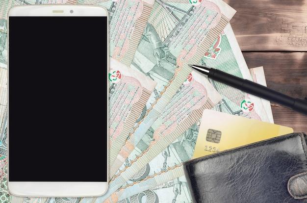 タイバーツ紙幣と財布とクレジットカード付きのスマートフォン