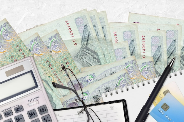 Thai baht bills and calculator with glasses and pen