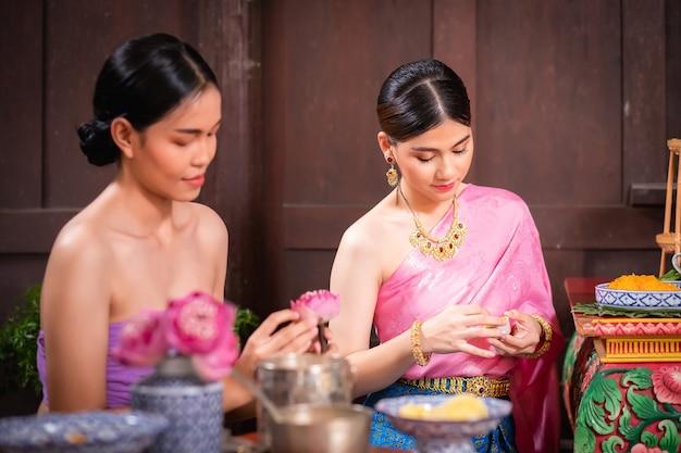タイの美しい女性と彼女は伝統的なタイのドレスを着ています。彼らは木製のキッチンで花、デザート、おやつを準備して座っていました。アユタヤの人々の過去の生活の概念