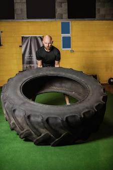 Тайский боксер поднимает тяжелую шину