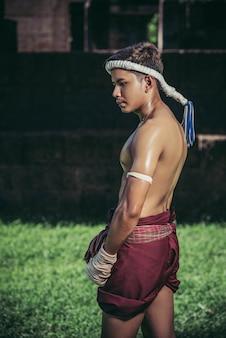 タイのボクサーは手でテープを包み、芝生の上に立ちます。
