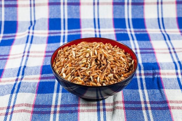 Ягоды тайского коричневого риса на фоне тайской ткани