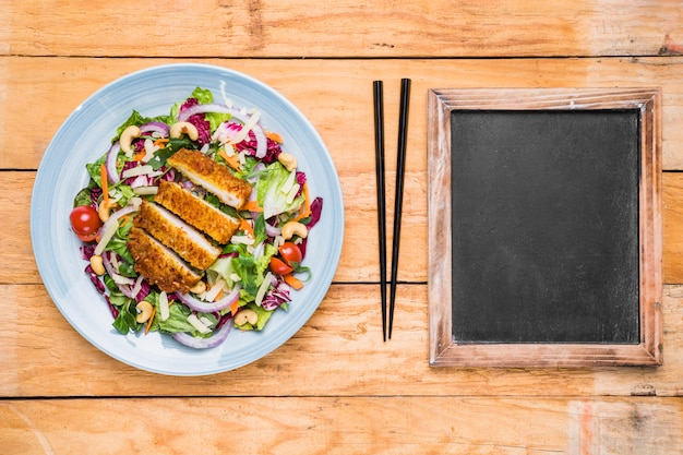 Thai chicken salad; chopstick and blank slate on wooden table
