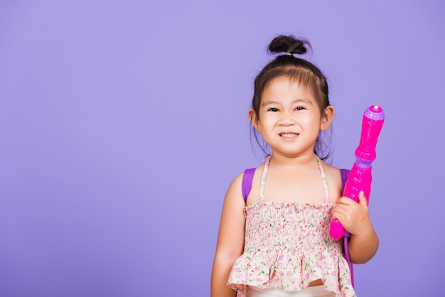 Thai child funny hold toy water pistol and smile, thailand songkran festival day