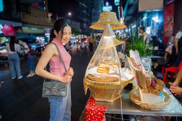 Тайско-китайские туристы прогуливаются и пробуют уличную еду на улице яоварат, китайский квартал, бангкок.