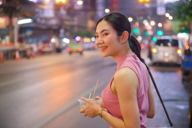 タイと中国の観光客がバンコクのチャイナタウンのヤワラー通りを散歩して屋台の食べ物を試食