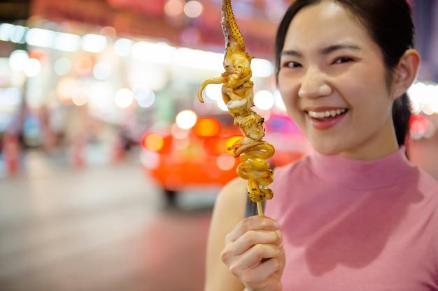 Thai-chinese tourists stroll around and sample street food at yaowarat road, chinatown, bangkok