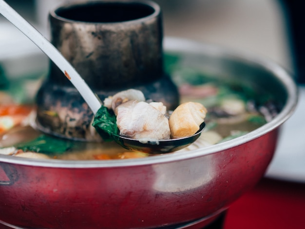 Thai clear soup spicy tom yum seafood in hot pot.