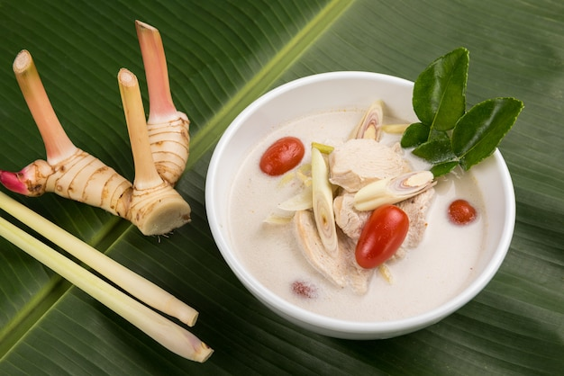 Thai coconut chicken soup (tom kha kai) in bowl with herb on banana leaf