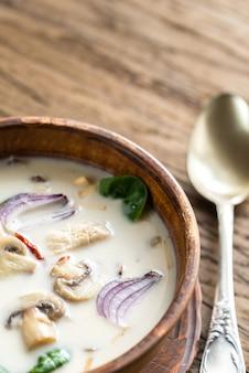 木製の背景にタイのココナッツクリームスープ