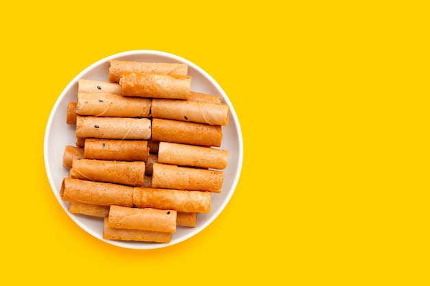 黄色の背景に白いプレートでタイのクリスピーココナッツロール。