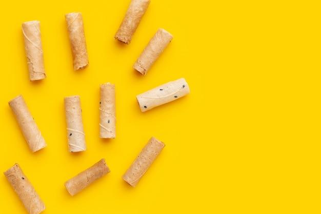 黄色の背景にタイのクリスピーココナッツロール。
