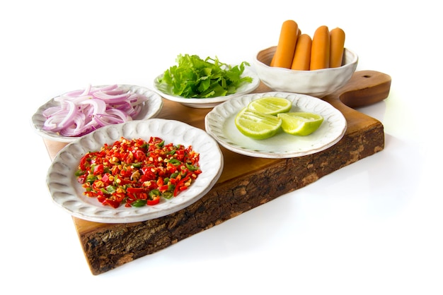 Thai cuisine ingredient of sausage spicy salad shallots, salari, lemon, chili, salted egg on chopping wood