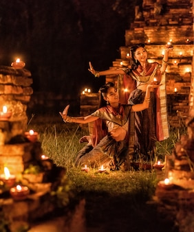 Thai dancing girl in ayutthaya style dress with candle at night