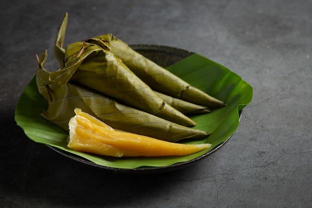 Dessert tailandese. pasticcini al vapore di melone avvolti in cono di foglie di banana