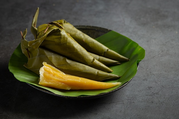 Тайский десерт. пирожное с канталупой, завернутое в конус банановых листьев