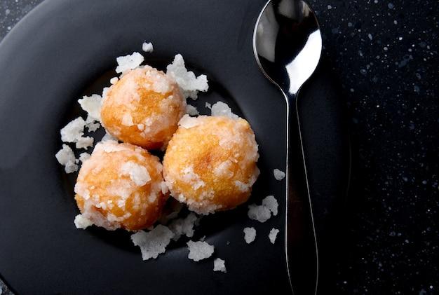 태국 디저트 khai hong은 쌀가루 녹두와 설탕 덮개로 만든 백조 알을 차 브레이크 스타일로 검정 접시에 올려놓은 것을 의미합니다.