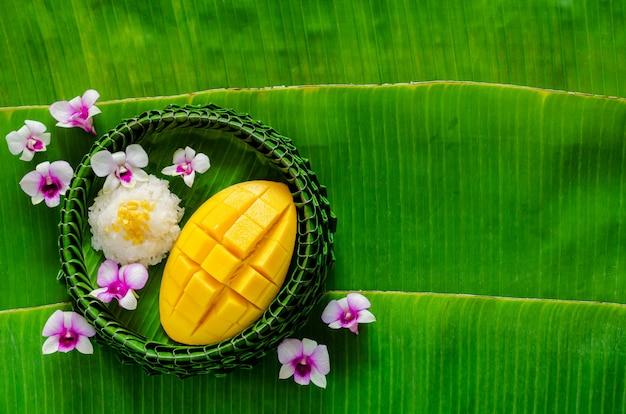 Тайский десерт - липкий рис с манго на тарелке из банановых листьев кладет на фон из банановых листьев с орхидеями.