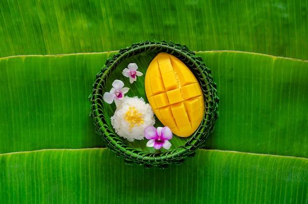 Тайский десерт - липкий рис с манго на тарелке из банановых листьев кладет на фон из банановых листьев.