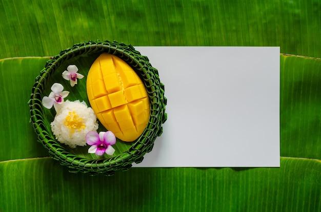 Тайский десерт - липкий рис с манго на тарелке из банановых листьев кладет на белый чистый лист бумаги и фон из банановых листьев.