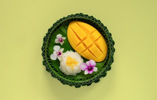 Тайский десерт - липкий рис с манго на тарелке из банановых листьев на желтом фоне.